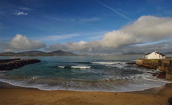 coastal scene with waves breaking on a sandy beach and hills in the background and a white cottage /