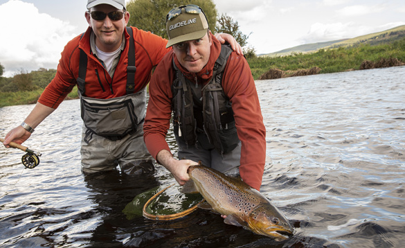 Two anglers releasing a brown trout into a river in Ireland/
