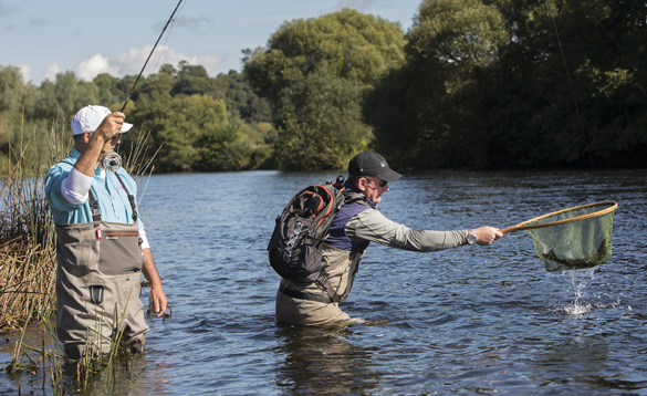 Two anglers fishing in a river in Ireland/