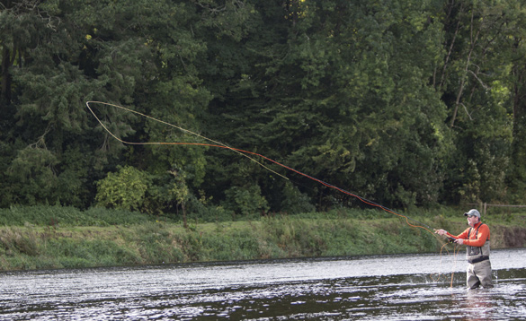 Angler stood in a river in Ireland fly fishing/