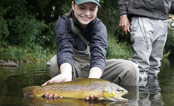 Young girl holding a brown trout caught in a river in Ireland/