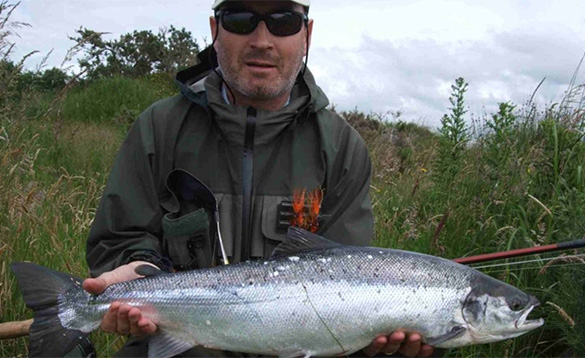 angler holding a recently caught salmon/