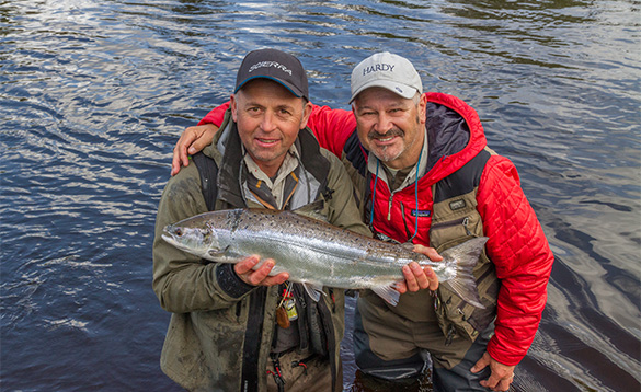 Two anglers beside a river, one holding a salmon/