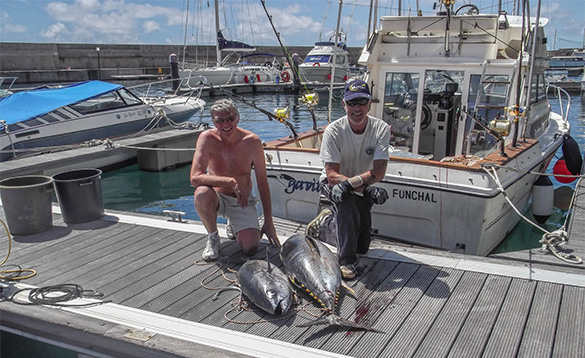 Two anglers on a wooden jetty beside a fishing boat with two yellowfin tuna/