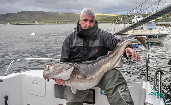angler sitting on a boat holding a recently caught cod/