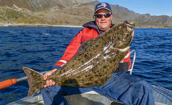 angler sitting on a boat holding a recently caught halibut/
