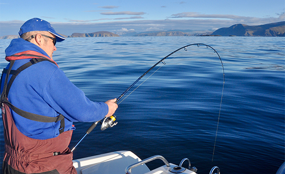 Angler fishing from a boat in a fjord in North Norway/
