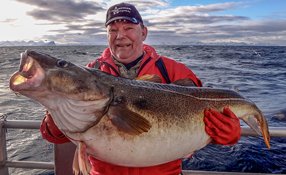 Angler holding a big cod on a boat in a fjord/