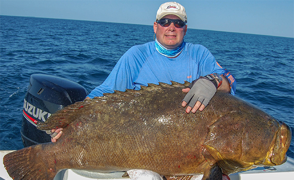 Angler sat on a boat holding a Goliath Grouper fish caught in Panama/