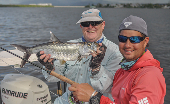 Two anglers sitting on a boat with one holding a tarpon fish caught in Puerto Rico/