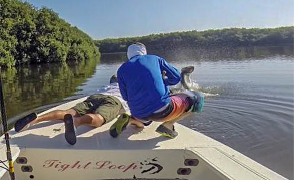 Two anglers on a boat in Puerto Rico with large tarpon leaping out of the water/