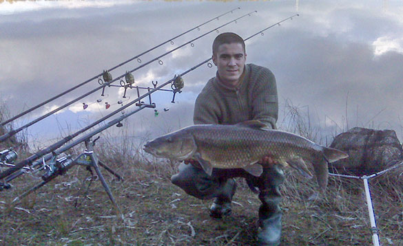 Angler holding a barbel beside a lake in Spain/