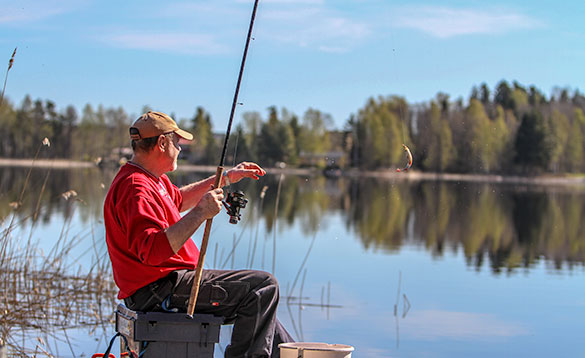 Angler fishing at the edge of a lake in Varmland, Sweden/