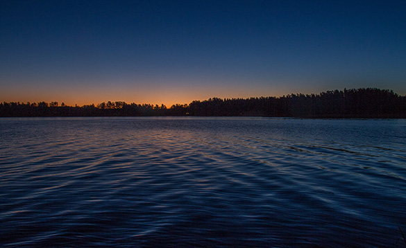 Sun setting behind forests next to a lake in Sweden/
