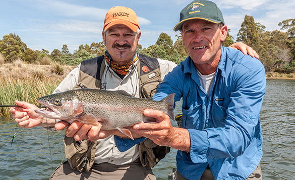 anglers hold a nice lake caught rainbow trout/