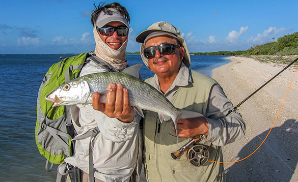 Two anglers holding a bonefish caught in the Cayman Islands/