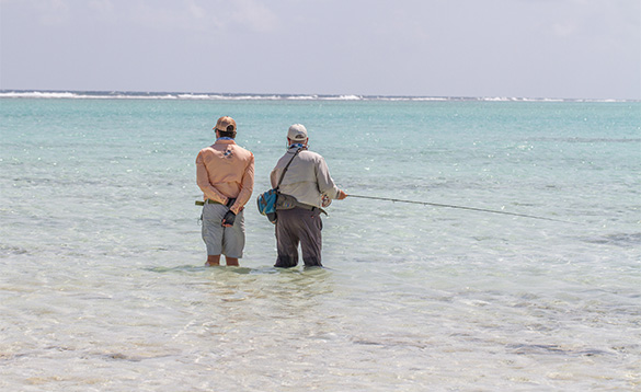 Two anglers standing in the sea around the Cayman Islands fishing/