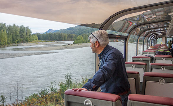 Man standing on a train looking at a view of a river in Alaska with forests and mountains in the background/