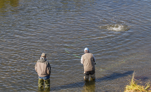 One angler watching another angler fly fishing in Alaska/